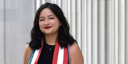 Image of a smiling person with dark shoulder-length hair, wearing red lipstick, standing in front of white marble columns. Photo Credit: Liz Wahid